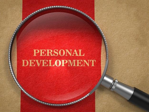 Концепция личного развития. увеличительное стекло на старой бумаге с красным фоном вертикальной линии.