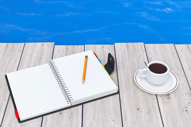 Personal diary or organiser book with pencil and cup of coffee in front of ocean extreme closeup.
