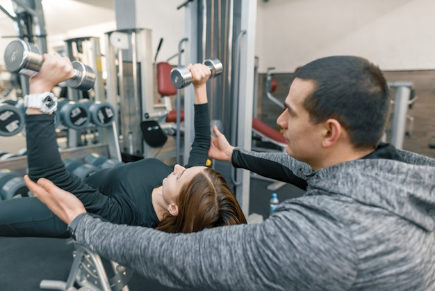 Personal fitness instructor training young woman in gym