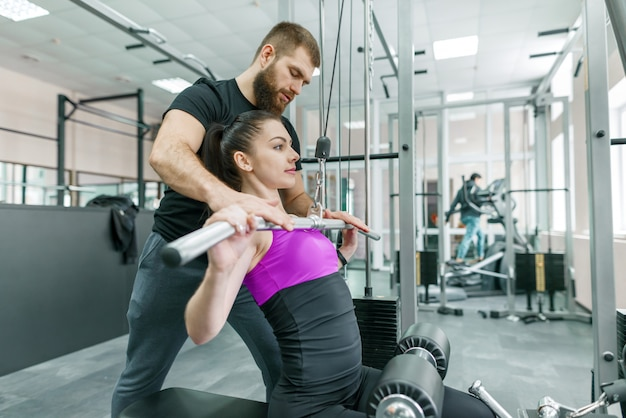 Personal fitness trainer coaching and helping client woman