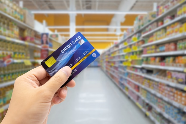 Personal hand holding credit card, with abstract blurred supermarket view of empty supermarket