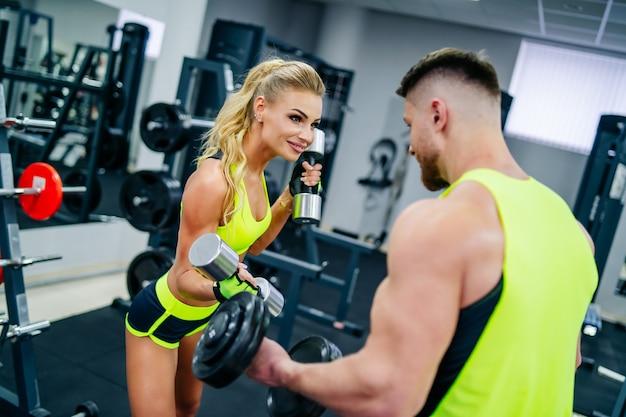 Персональный красивый фитнес-тренер и красивая блондинка женщина-клиент в тренажерном зале, развлекаясь во время тренировки. концепция здорового образа жизни.