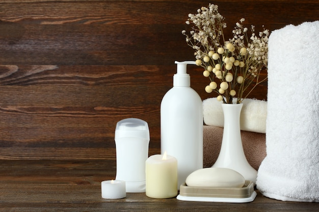 Personal hygiene items with decorative sprigs on a brown wooden background