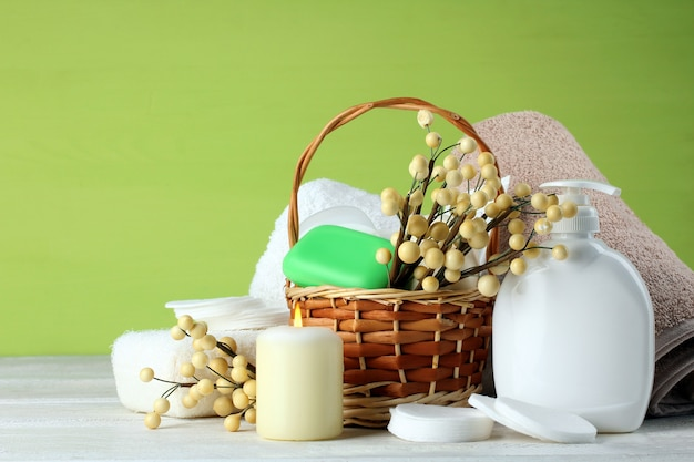 Personal hygiene items with decorative sprigs on a white wooden background