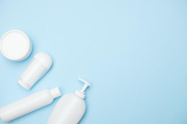 파란색 배경, 복사 공간, 평면도에 개인 위생 제품 흰색 항아리. 고품질 사진