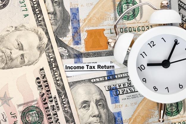 Personal income tax form 1040, dollar bills, alarm clock.