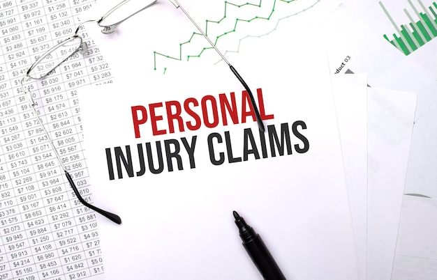 Personal injury claims . conceptual background with chart ,papers, pen and glasses