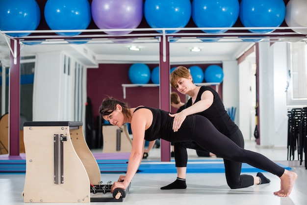 Personal instructor supervising young woman exercising on combo wunda pilates chair