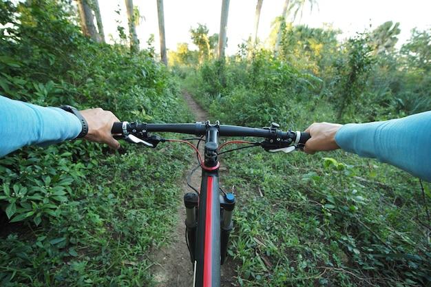 Личный перспективный снимок человека, катающегося на горном велосипеде в тропической среде