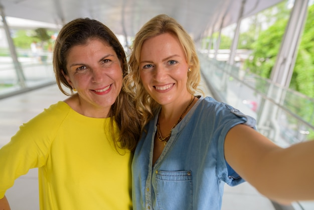 Personal point of view of two happy woman taking selfie