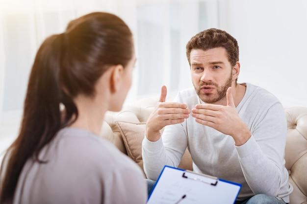 Личные проблемы. симпатичный бородатый безрадостный мужчина жестикулирует и пытается объяснить свою проблему во время разговора с психологом