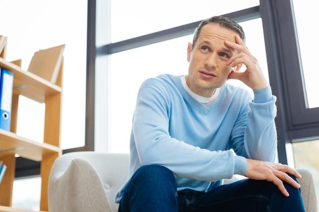 個人的な問題。肘掛け椅子に座って、落ち込んでいる間彼の額を保持している不幸な悲しいハンサムな男
