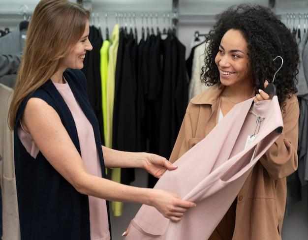 Personal shopper che aiuta il cliente a scegliere i vestiti
