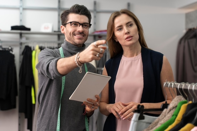 Personal shopper helping cutomer to choose clothes