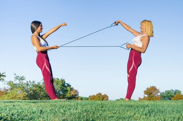 Personal sports and fitness trainer dressed in sportswear trains a blond senior woman with healthy lifestyle outdoors performing stretching with rubber bands smiling happy during exercise