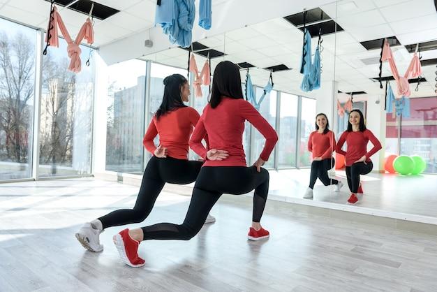 明るいジムでエクササイズフィットネスのためにウォーミングアップする女性を支援するパーソナルトレーナー。健康的な生活様式