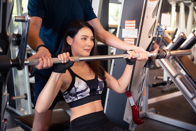 Personal trainer or athlete teach young asian woman with barbell fitness training at gym