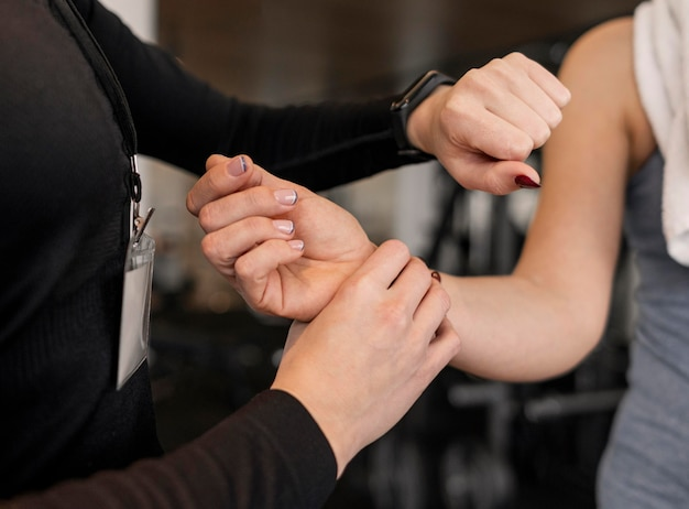 Personal trainer checking her client arm