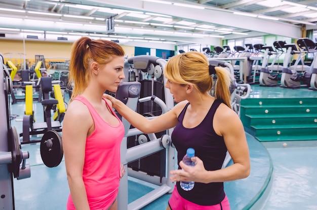 체육관에서 힘든 훈련을 한 후 슬픈 젊은 여성을 격려하는 개인 트레이너