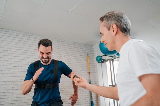 Персональный тренер подбадривает молодого человека, который тренируется во время бега