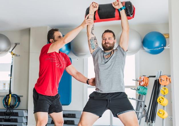 Персональный тренер помогает мужчине, который тренируется с весовой сумкой в тренажерном зале