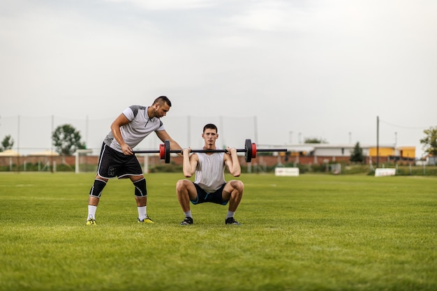 Personal trainer helping his trainee to lift up dumbbell while standing on soccer field.
