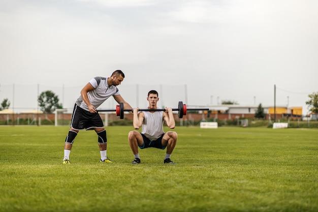 Персональный тренер помогает своему ученику поднимать гантели, стоя на футбольном поле.