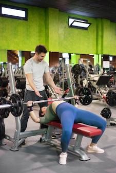 Личный тренер помогает женщине в тренажерном зале.