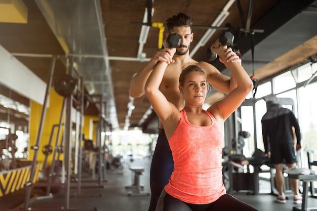Персональный тренер помогает женщине в тренажерном зале
