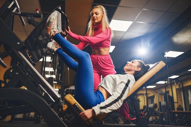 Персональный тренер помогает женщине в тренировках на тренажере внутри фитнес-центра, концепция спортивного образа жизни и бодибилдинга
