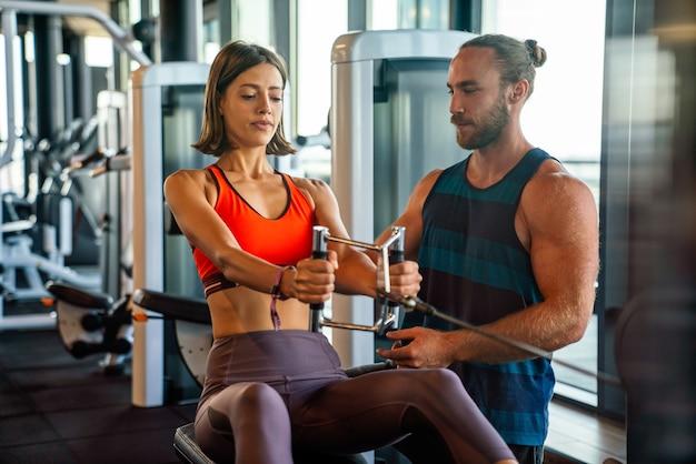 Персональный тренер помогает женщине, тренирующейся в спортивном тренажерном зале