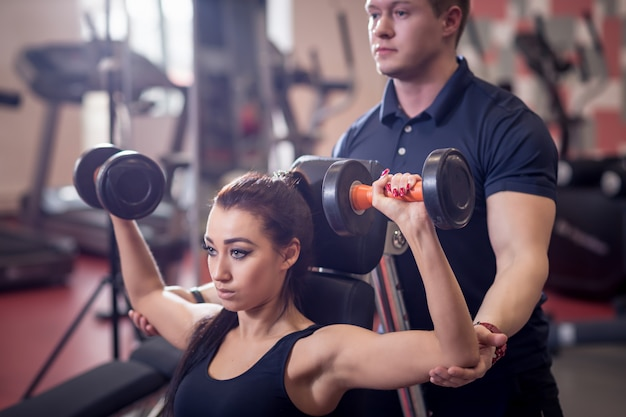 重いダンベルで働く女性を助けるパーソナルトレーナー