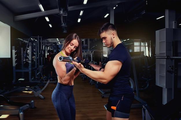 개인 트레이너는 체육관에서 운동하는 소녀를 도와줍니다.