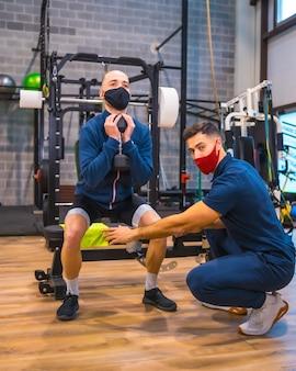 코로나 바이러스 전염병에서 운동 선수의 스쿼트를 교정하는 체육관의 개인 트레이너