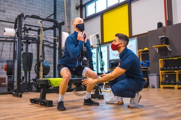 코로나 바이러스 전염병에서 젊은 운동 선수의 스쿼트를 교정하는 체육관의 개인 트레이너