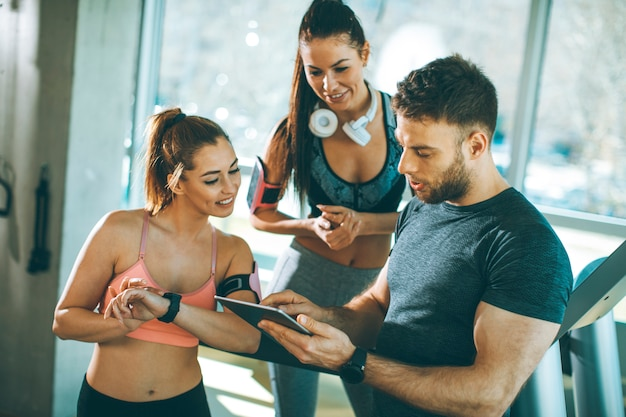 Personal trainer looking at digital tablet and explaining progress to young women at the gym