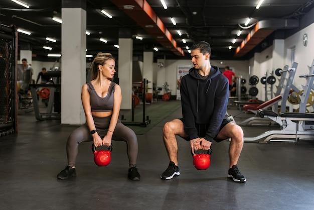 パーソナルトレーナーは、スポーツのバックグラウンドでケトルベルを使ってしゃがむ方法を女性に示します。