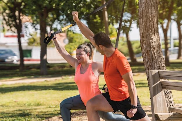 都市公園の女性に正しいtrx運動位置を教えるパーソナルトレーナー。