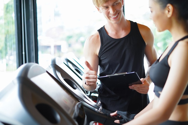 Personal trainer thumb up and cheer fitness center customer