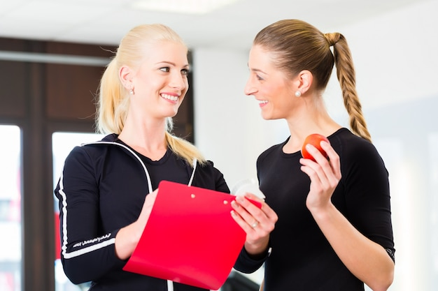 Personal trainer with woman in fitness studio