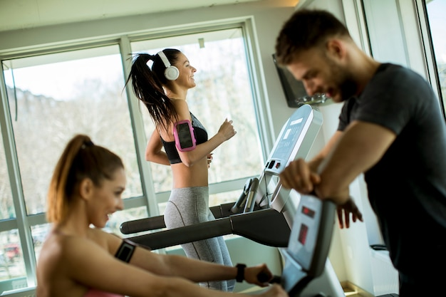 Personal trainer with young woman on cycling machine at the gym