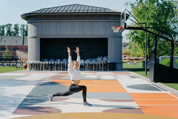 Personal workout routine. athletic woman does physical exercises outdoor keeps arms raised up warms up before jogging dressed in active wear poses on basketball court. flexibility and fitness