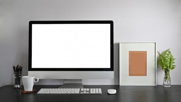 빈 화면, 연필 홀더, 액자, 화분 및 커피 컵 흰색 벽과 현대 나무 테이블에 함께 넣어 개인 작업 공간 컴퓨터
