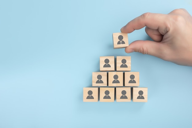 Personnel pyramid. human resources, corporate hierarchy concept and multilevel marketing - recruiter complete team represented by wooden cube by one leader person.