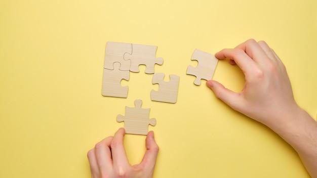 人は木製のパズルを組み立てて、最後のピースを接続します。スタッフのチームワーク。