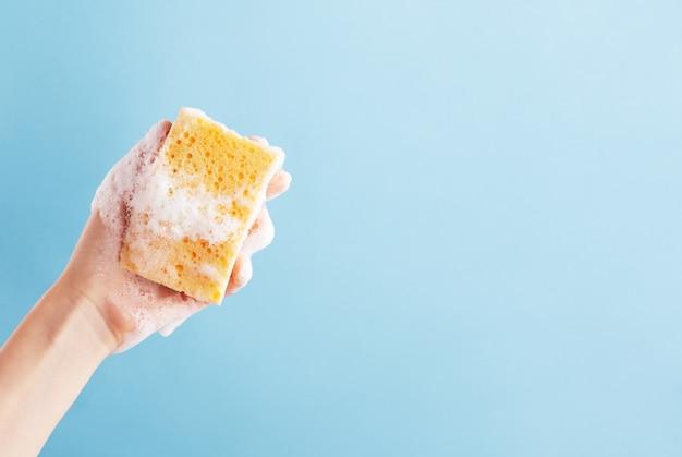 Лица руки, держащей желтую губку для мытья посуды. мочалка в мыле.