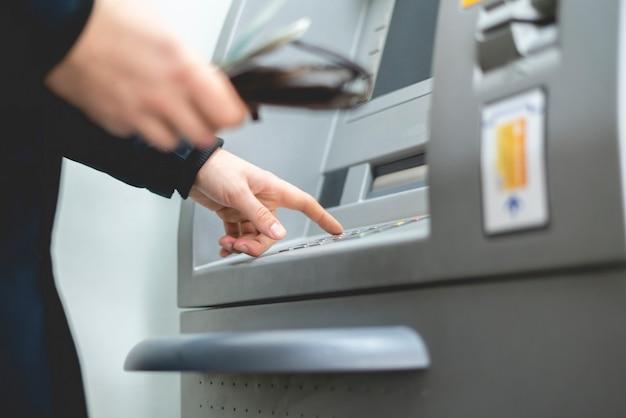 現金自動支払機にカードを手で挿入する人b