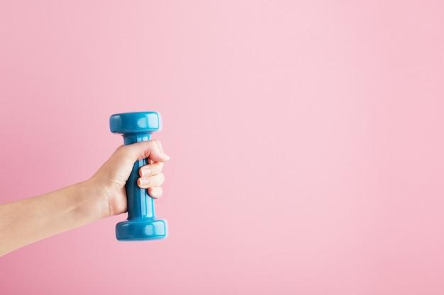 青いダンベルを手で持ち上げる人。家庭やジムでのトレーニング用のフィットネス機器。