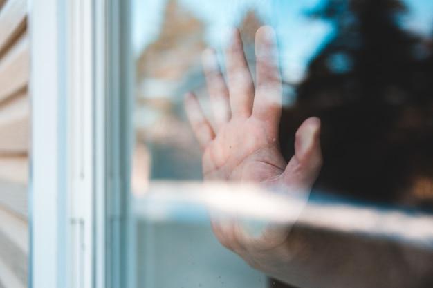 人はガラス窓に手を