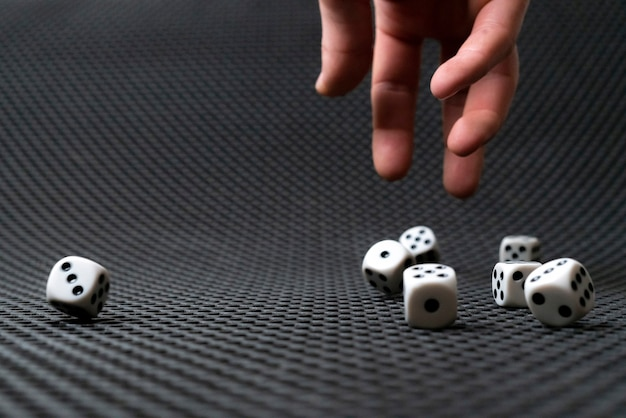 A persons hand roll the dice cubes on the table win gamble casino
